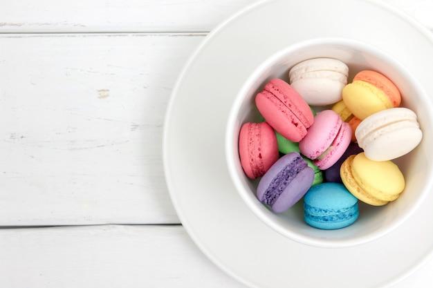 Macarons coloridos en una taza con pastel vintage filtrada