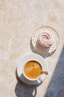 Macarons dulces sabrosos y taza de café fondo beige. vista superior tarjeta de felicitación concepto de día de san valentín, tazas tazas de café luna de miel boda mañana desayuno sorpresa, colores pastel copia espacio, luz