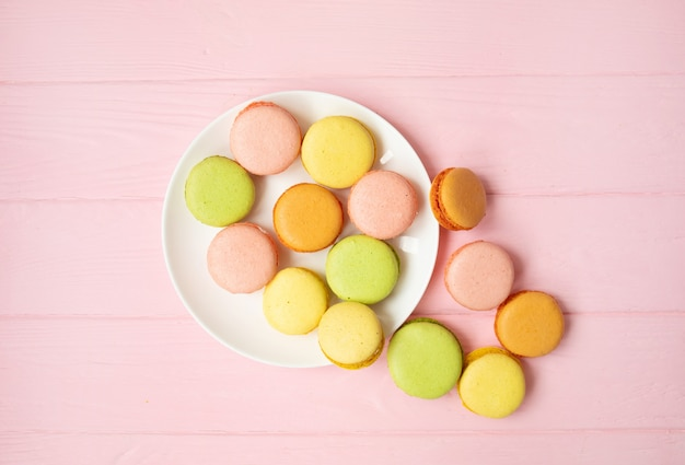 Los macarons franceses o italianos coloridos apilan en la placa blanca puesta en la tabla de madera rosada con el espacio de la copia para el fondo. postre servido con té de la tarde o pausa para el café.