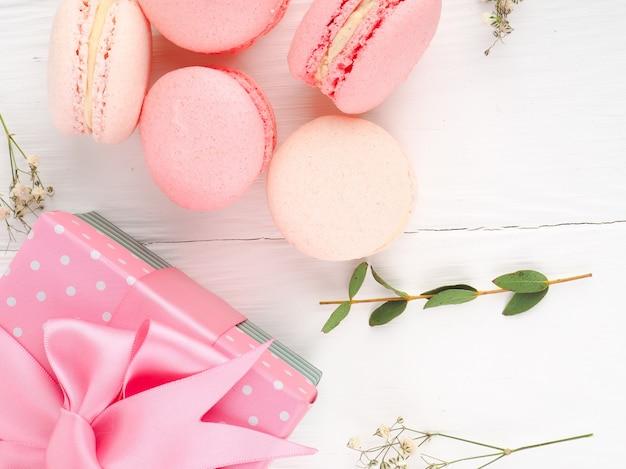 Los macarons franceses o italianos coloridos apilan en la tabla de madera blanca. postre para servir con merienda o café