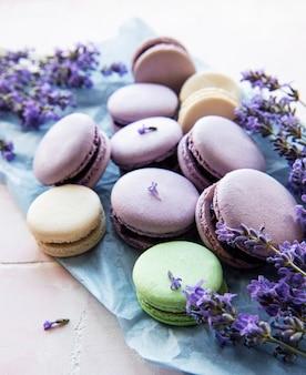 Macarons franceses con sabor a lavanda y flores frescas de lavanda sobre un fondo de mosaico