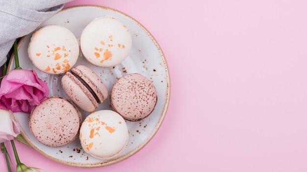Macarons en plato con rosas y espacio de copia