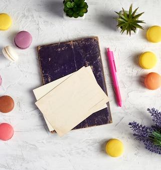 Macarons redondos al horno, postales vacías, cuaderno, bolígrafo rosa