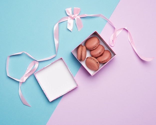 Macarons redondos multicolores horneados en cajas cuadradas sobre un pastel de color