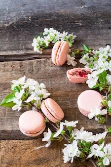 Macarons rosados con ganache de chocolate, caramelo y frambuesa. rama floral. postre francés delicado. macarrones de frambuesa. postre de boda primavera.