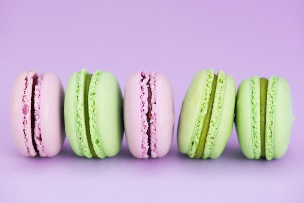 Macarons rosados y verdes en la fila