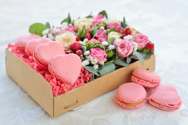 Macarrón francés en forma de corazón de san valentín, la caja con flores, rosas rosadas