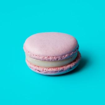 Macarrón rosa con crema sobre fondo azul