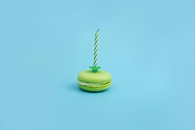 Macarrón verde con una vela sobre un azul