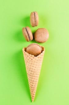 Macarrones de chocolate en un cono de waffle en un copyspace verde, vista superior, flatley con copyspace