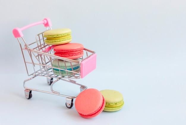 Macarrones de colores en un carrito de compras sobre un fondo azul.