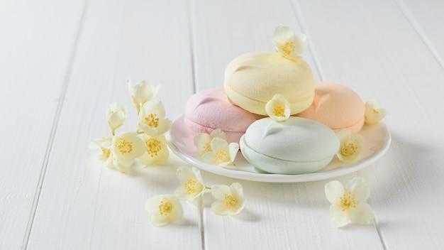 Macarrones de colores con flores de jazmín en una mesa blanca.