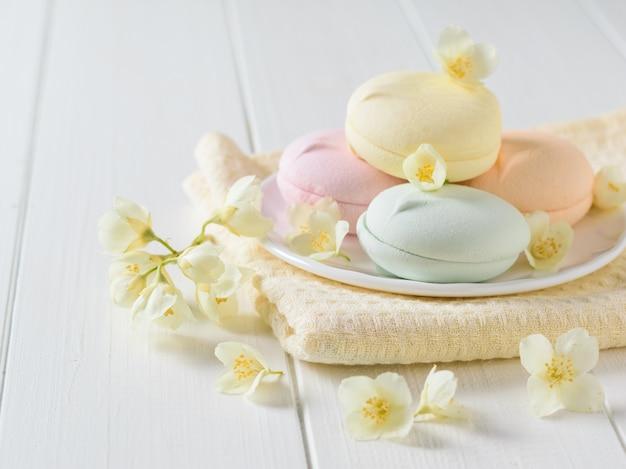 Macarrones de colores con flores de jazmín en una mesa rústica blanca.