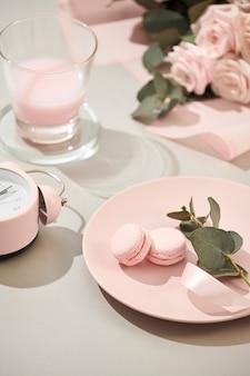 Macarrones en colores pastel con ramo de flores rosas rosadas aisladas