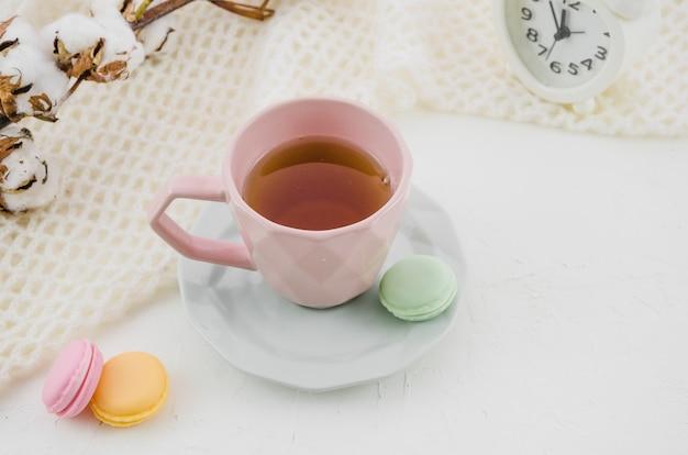 Macarrones coloridos con té verde herbario en taza y platillo rosados de la cerámica en el escritorio