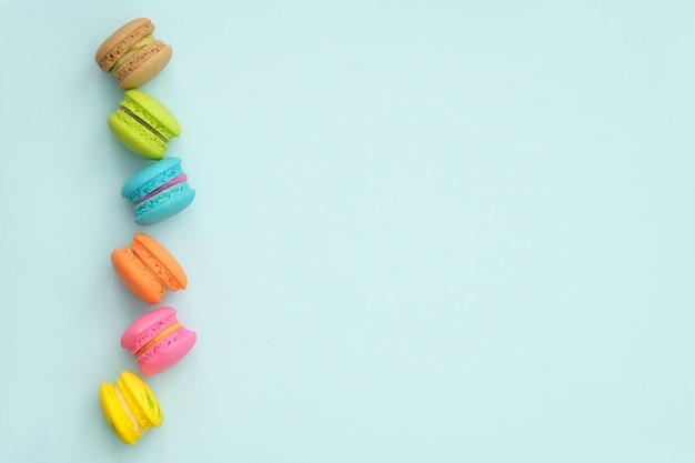 Macarrones coloridos de la visión superior postre en fondo de la turquesa.
