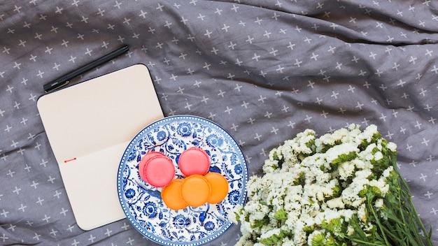 Macarrones; diario; bolígrafo y ramo de flores blancas sobre textil gris.
