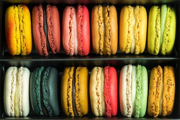 Macarrones franceses coloridos mezclados en caja. fondo de patrón de comida dulce.