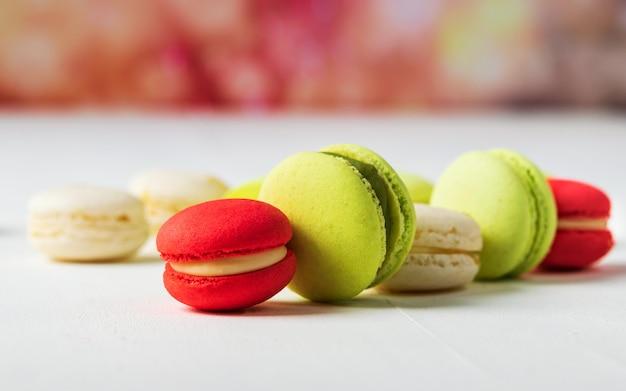 Macarrones franceses dulces y coloridos en bandera colorida del fondo con el espacio de la copia.