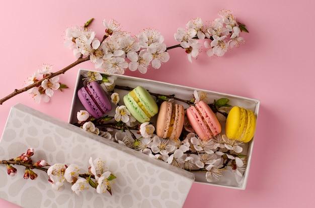 Macarrones frescos en una caja de regalo con flores de albaricoquero en rosa pastel