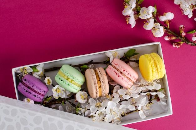 Macarrones frescos en una caja de regalo con flores de albaricoquero