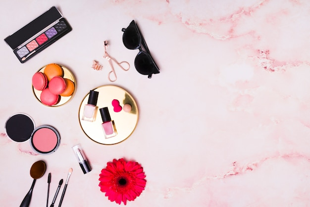 Macarrones; gafas de sol y productos cosméticos sobre fondo rosa texturado.
