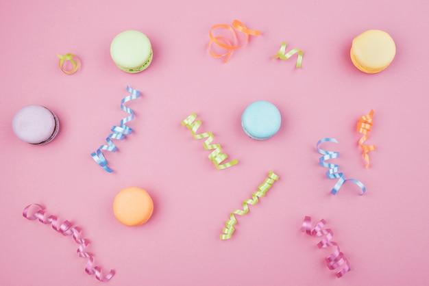 Macarrones multicolores con confeti sobre fondo rosa