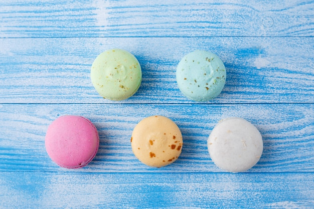 Macarrones multicolores sobre superficie azul,