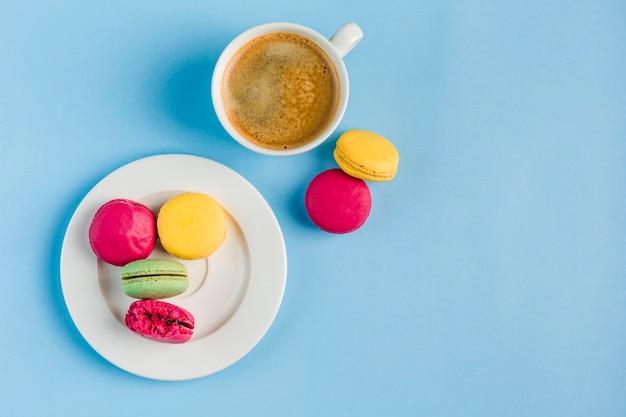 Macarrones multicolores con una taza de café blanco sobre un copyspace azul, vista superior, plano con copyspace