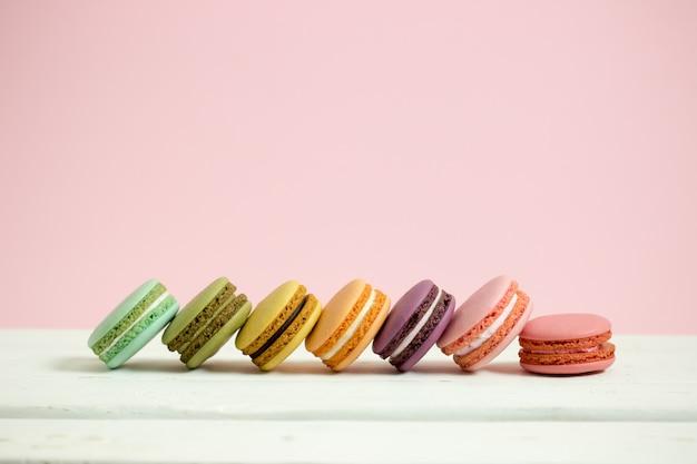 Macarrones o macaron franceses dulces y coloridos en el fondo de madera blanco del rosa de la tabla, postre.