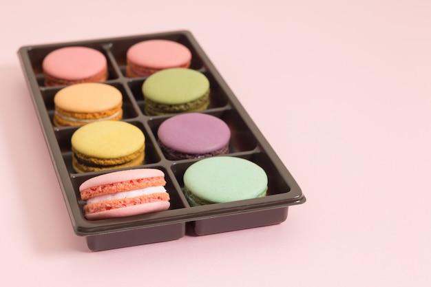 Macarrones o macaron franceses dulces y coloridos en el fondo rosado, postre.