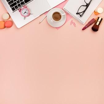 Macarrones, pinceles de maquillaje con reloj despertador en la computadora portátil y papelería sobre fondo de melocotón