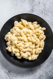 Macarrones con queso. pasta de macarrones en salsa de queso. fondo gris vista superior