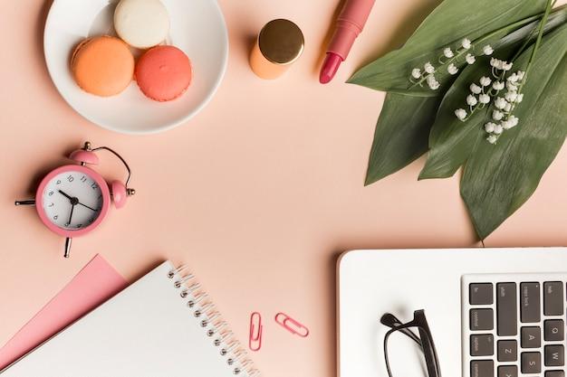 Macarrones, reloj despertador, lápiz labial, hojas y flores con bloc de notas en espiral y computadora portátil