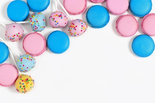 Macarrones rosados y azules y estallidos de la torta en blanco