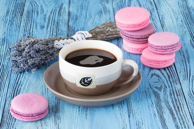 Macarrones rosados y taza de café cerca de levender seco