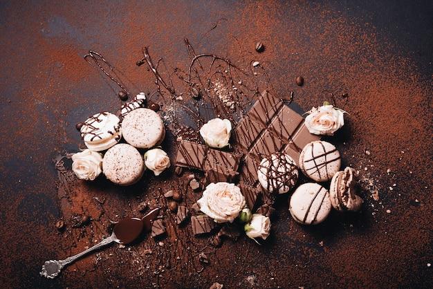 Macarrones; rosas rosadas; barra de almíbar y chocolate espolvoreada con polvo de café sobre fondo negro oscuro