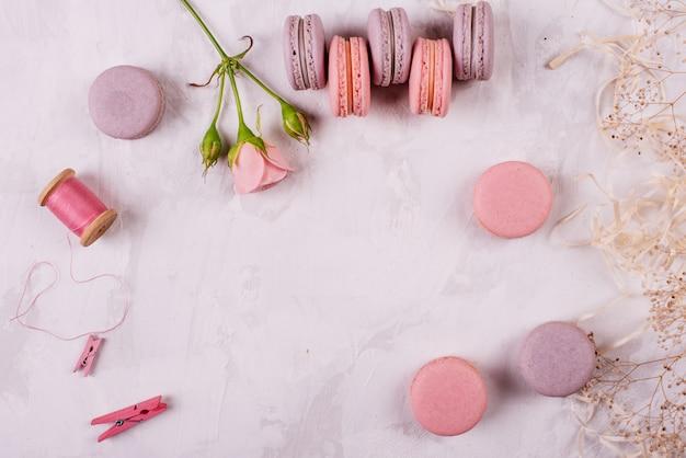 Macarrones sabrosos rosados hermosos en un fondo concreto