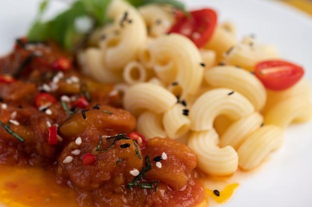 Macarrones salteados con tomate, chile, pimiento y albahaca en un plato blanco.
