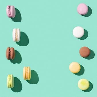 Macarrones surtidos sobre fondo de color verde azul brillante, coloridos macarons de galletas francesas
