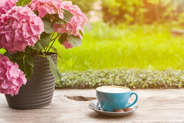 Maceta rosada hermosa y taza de café en superficie de madera