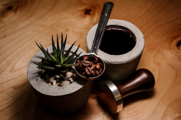 Macetas de hormigón de moda y lindas con bebida de café y planta