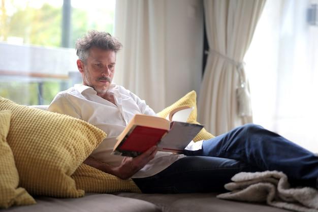Macho adulto acostado en el sofá y leyendo un libro bajo la luz del sol a través de las ventanas
