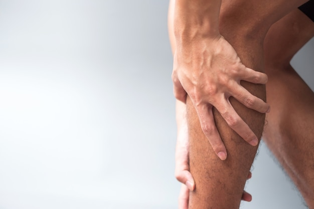 Macho adulto con dolor muscular sobre fondo gris. anciano con dolor en la pierna debido al tirón del músculo de la pantorrilla. lesiones deportivas y concepto médico.