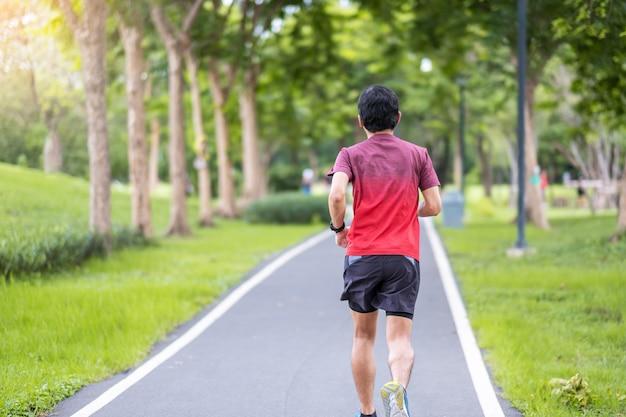 Macho adulto joven en ropa deportiva corriendo en el parque