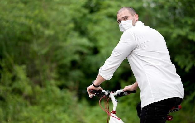 Macho adulto montando bicicleta con mascarilla