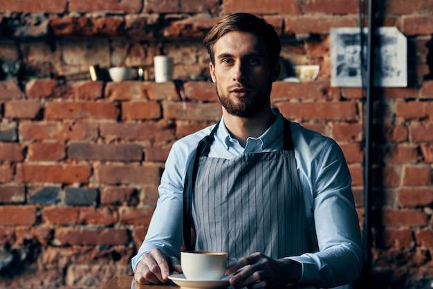 Macho camarero delantal servicio taza de café pared de ladrillo