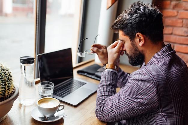 Macho estudiante cansado en eyeglases en la cafetería, usando la computadora portátil