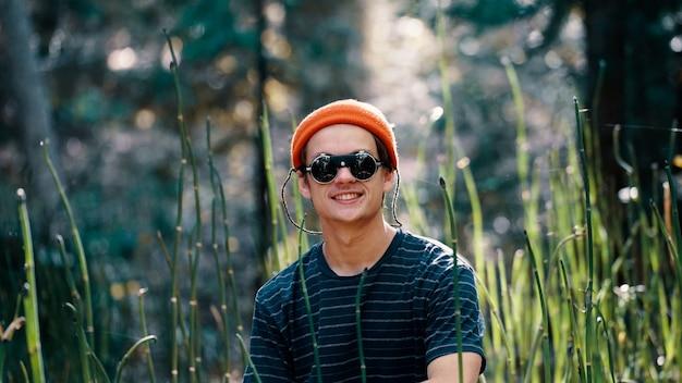 Macho con gafas de sol y un sombrero naranja