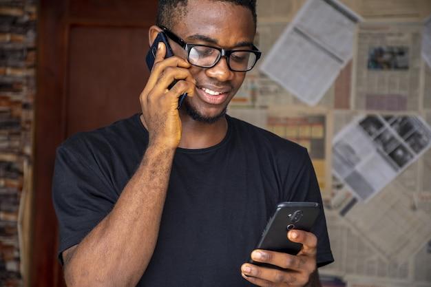 Macho joven africano con gafas hablando por teléfono mientras usa otro en una habitación